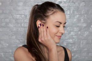 Femme se touchant l'oreille